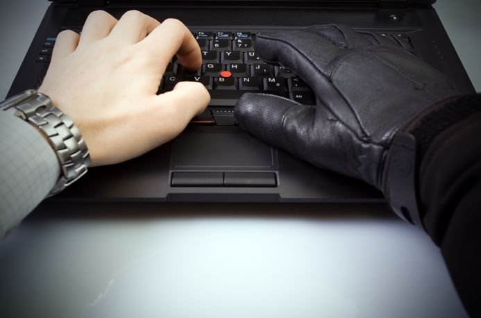 Employee using laptop. One hand bare, the other with a glove to symbolize fraudulent activity.